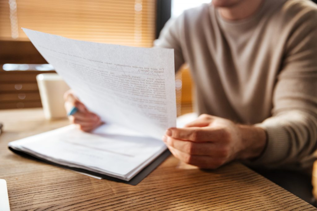 cropped photo of young man reviewing a document in one hand and holing a pen in the other on top of more documents