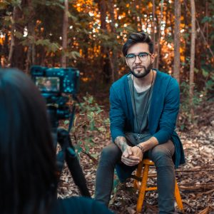 a male subject is being interviewed in a forest by a female interviewer with DSLR camera and tripod